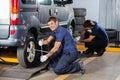 Happy mechanic fixing car tire at repair shop portrait of male auto Stock Image