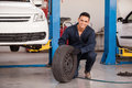 Happy mechanic loving his job handsome young removing a tire from a car at an auto shop and smiling Royalty Free Stock Photos