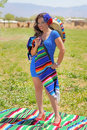 Happy mexican pin up girl attractive latina standing in a farm field holding a colorful blanket and sombrero Stock Photography