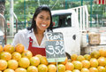 Happy mexican saleswoman with oranges on a farmers market Royalty Free Stock Photo