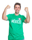 Happy mexican sports fan from mexico with a green jersey on an isolated white background is about a goal of his national team Stock Photos