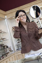 Happy mid adult woman trying on glasses while looking into hand mirror Royalty Free Stock Photography