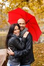 Happy middle aged couple on autumn day with umbrella outdoors beautiful rainy Stock Photos