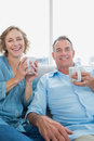 Happy middle aged couple sitting on the couch having coffee smiling at camera at home in living room Stock Images