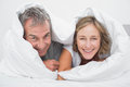 Happy middle aged couple under the duvet smiling at camera in bedroom at home Stock Photo