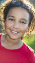 Happy mixed race african american girl child outdoor portrait of a beautiful young interracial smiling backlit in sunshine with Royalty Free Stock Photography