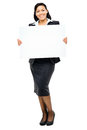 Happy mixed race business woman pointing at empty copy space iso holding white placard Stock Images