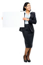 Happy mixed race business woman pointing at empty copy space iso holding white placard Royalty Free Stock Image