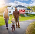 Happy Mixed Race Family in Front of Home and For Sale Sign Royalty Free Stock Photo