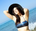Happy model with hat in the water tanning with bikini happiness vacation holiday travel fun Royalty Free Stock Photography