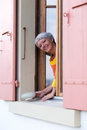 Happy modern senior woman with white hairs looking from the window Royalty Free Stock Photo