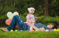 Happy mom and baby are playing in the park on green grass Royalty Free Stock Photos