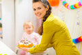 Happy mom carries birthday cake for baby Royalty Free Stock Photography