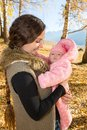 Happy mom and child girl hugging and laughing on nature fall. Royalty Free Stock Photos
