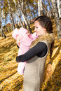 Happy mom and child girl hugging and laughing on nature fall the concept of cheerful childhood and family beautiful mother her Royalty Free Stock Images