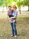 Happy mom holding son outdoors in a park Stock Images