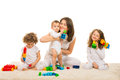 Happy mom and kids home playing with building blocks sitting together on carpet Royalty Free Stock Images