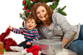 Happy mom and son celebrate first christmas in front of xmas tree Stock Images