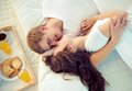 Happy morning female and her husband enjoying one another in bed Royalty Free Stock Images