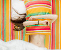 Happy morning girl moments lying on the bed covered his head with a pillow fooling around bare beautiful slim belly top view Royalty Free Stock Images