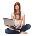 Happy mother with adorable little girl and laptop childhood parenting technology concept Stock Photo