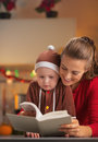 Happy mother and baby in christmas costume reading book decorated kitchen Royalty Free Stock Photography