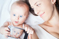 Happy mother with a baby lying on a white bed funny girl make selfie mobile phone and near her newborn looking at the camera and Stock Photography
