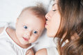 Happy mother with a baby lying on a white bed newborn girl near her mum kissing her daughter mothercare is most important in life Royalty Free Stock Photo