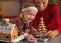 Happy mother and baby making christmas cookie house in kitchen decorated Stock Photos