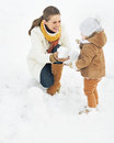 Happy mother and baby making snowman in winter park high resolution photo Royalty Free Stock Photos