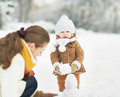 Happy mother and baby making snowman in winter park high resolution photo Royalty Free Stock Photography