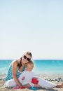 Happy mother and baby playing on beach Stock Photography