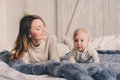 Happy mother and baby playing at home in bedroom. Cozy family lifestyle Royalty Free Stock Photo