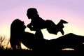 Happy mother and baby playing outside silhouette a of a laughing mom is laying in the grass at sunset lifting her boy up into the Royalty Free Stock Image