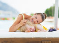 Happy mother and baby playing at poolside high resolution photo Stock Image