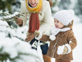 Happy mother and baby playing with snow on branch high resolution photo Stock Image