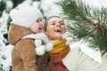 Happy mother and baby playing with snow on branch high resolution photo Royalty Free Stock Images