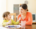 Happy mother and baby plays with watercolor in home focus on women only Stock Image