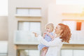 Happy mother with baby standing in front of house building and pointing on copy space Stock Images