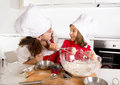 Happy mother baking with little daughter in apron and cook hat with flour dough at kitchen Royalty Free Stock Photo