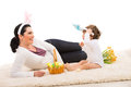 Happy mother and boy with easter basket toddler bunny ears sitting on carpet Stock Photos