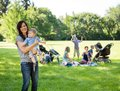 Happy mother carrying baby boy at park portrait of with friends and children in background Stock Photo