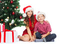 Happy mother and child boy with gift boxes holidays presents christmas x mas concept in santa helper hats Royalty Free Stock Images