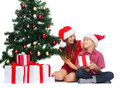 Happy mother and child boy with gift boxes holidays presents christmas x mas concept in santa helper hats Stock Photos