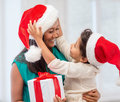 Happy mother and child girl with gift box holidays presents christmas x mas concept in santa helper hats Royalty Free Stock Images