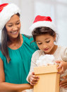 Happy mother and child girl with gift box holidays presents christmas x mas concept in santa helper hats Royalty Free Stock Photos