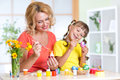 Happy mother and child girl preparing to Easter holiday and with brush coloring eggs