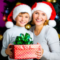 Happy mother with child hold box with gift on the christmas holiday indoors Royalty Free Stock Photos