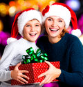 Happy mother with child hold box with gift on the christmas holiday indoors Stock Photos