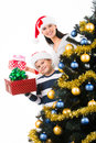 Happy mother with child hold box with gift near the christmas tree Stock Photo